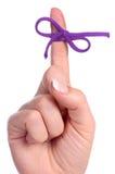 Um dedo contem uma corda curvar-amarrada como um lembrete fotografia de stock