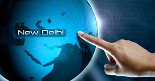 Um dedo da mulher e um globo, Nova Deli Imagens de Stock