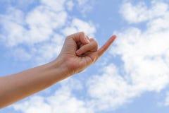 Um dedo mínimo e uma mão que alcançam para o fundo do céu azul Imagem de Stock Royalty Free