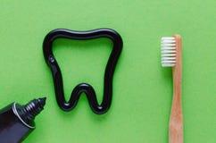 Um dente do dentífrico, dentes importa-se o conceito, escova de dentes no fundo verde fotos de stock
