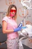 Um dentista da menina que veste vidros vermelhos e uma lâmpada da foto em suas mãos, sorrindo no escritório dental imagens de stock royalty free