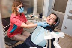 Um dentista examina os dentes do seu paciente Ação na clínica dental Foto de Stock Royalty Free
