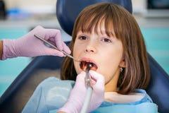 Um dentista trata os dentes das meninas no escritório dental fotografia de stock