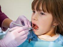 Um dentista trata os dentes das meninas no escritório dental foto de stock royalty free