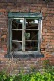 Um derelict idoso, quadro de janela verde rotted contra uma parede de tijolo vermelho imagem de stock royalty free