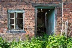 Um derelict idoso, uma janela verde rotted e um quadro de porta contra uma parede de tijolo vermelho, com plantas cobertos de veg fotos de stock royalty free