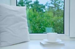 Um descanso branco, um livro e um copo e uns pires imagem de stock royalty free