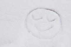 Um desenho de sorriso da cara na neve Fotografia de Stock