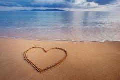 Um desenho de um coração em uma areia amarela em vagabundos bonitos de um seascape Imagens de Stock