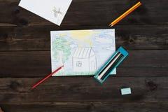 Um desenho do ` s das crianças tirado por lápis encontra-se em uma tabela de madeira Imagem de Stock