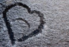 Um desenho sob a forma de um coração na neve caída no vidro do carro fotos de stock royalty free