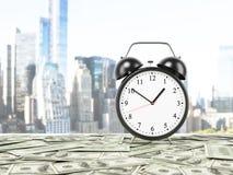 Um despertador é estabelecido na superfície que é coberta por notas do dólar Fotos de Stock