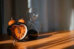 Um despertador alaranjado está na tabela Mostra o tempo de jantar foto de stock