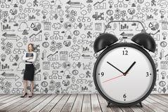 Um despertador enorme na vista dianteira e lá é uma senhora do negócio com arquivo de original preto Os ícones do negócio são tir Fotos de Stock Royalty Free