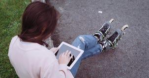 Um detalhe de moça com os patins bonitos do cabelo e de rolo que sentam-se na grama verde e que usam o toque do tablet pc vídeos de arquivo