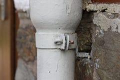Um detalhe de um parafuso de um conduto pluvial branco imagem de stock