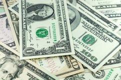 Um, dez e cem no fundo de muitos dólares Fotografia de Stock Royalty Free