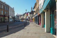 Um dia de verão ensolarado nas ruas de Greenwich, Londres com os povos não identificados que andam avante Imagem de Stock