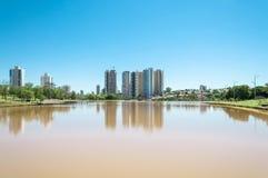 Um dia ensolarado bonito no lago com construções e o fundo da cidade Fotografia de Stock Royalty Free