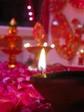 Um diya iluminado na cama de rosas imagem de stock royalty free
