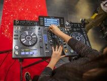 Um DJ fêmea que joga com um console pioneiro em Cagliari, Sardinia em novembro de 2018 imagens de stock