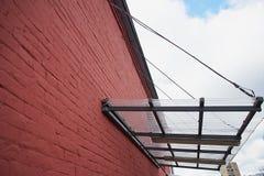 Um dossel feito do policarbonato em uma base do metal montou em uma parede de tijolo vermelho Foto de Stock