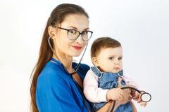 Um doutor da jovem mulher guarda um bebê em seus braços, sorri, e brincadeiras com um estetoscópio imagens de stock royalty free