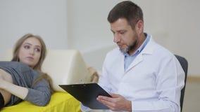 Um doutor examina uma mulher gravida e grava o testemunho em um informe médico filme