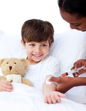Um doutor fêmea que dá a uma criança uma injeção Fotografia de Stock Royalty Free