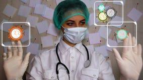 Um doutor novo com uma seringa que veste uma máscara examina video estoque
