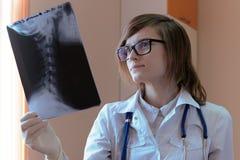 Um doutor novo em um vestido médico com vidros e em um estetoscópio em seu pescoço olha proximamente no raio X fotografia de stock
