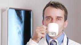 Um doutor novo que olha a câmera está bebendo uma bebida quente de uma caneca branca No pescoço pendura um estetoscópio Close-up video estoque