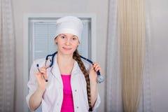 Um doutor ou uma enfermeira fêmea com um estetoscópio & um x28; ou phonendoscope& x29; suportes e sorrisos imagens de stock