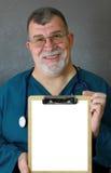 Doutor maduro de sorriso Indicação uma prancheta vazia Foto de Stock Royalty Free