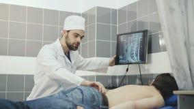 Um doutor que examine mostras de um paciente a espinha ferida no monitor 4K vídeos de arquivo