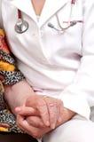 Um doutor que prende a mão de uma mulher adulta imagem de stock royalty free