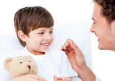 Um doutor que toma a temperatura do rapaz pequeno Fotografia de Stock Royalty Free