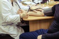 Um doutor, um trabalhador médico em um revestimento branco, medidas a pressão no braço de um homem que senta-se em uma cadeira em imagem de stock royalty free