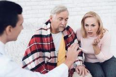 Um doutor veio ao ancião em um casaco de lã amarelo O doutor mostra o termômetro, a mulher está em choque imagem de stock
