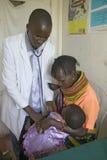 Um doutor verifica a mãe e as crianças para ver se há HIV/AIDS em Pepo La Tumaini Jangwani, programa de reabilitação da comunidad imagem de stock
