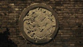 Um dragão chinês cinzelado fora da pedra em uma parede dentro de Hong Kong China imagens de stock