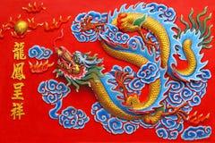 Um dragão dourado na parede vermelha. Fotografia de Stock