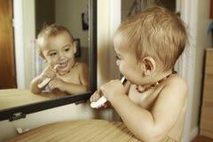 Um e meia menina do ano que escova seus dentes imagem de stock royalty free