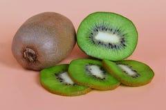 Um e meios frutos de quivi e três fatias, conceito saudável comer em um fundo alaranjado imagens de stock royalty free