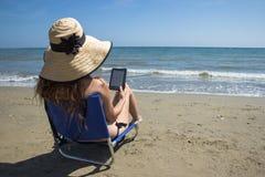 Um ebook da leitura da menina em uma cadeira na praia Foto de Stock