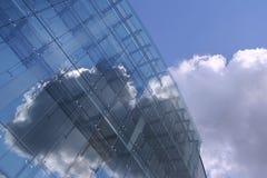 Um edifício futuro glassy no céu azul Fotografia de Stock Royalty Free