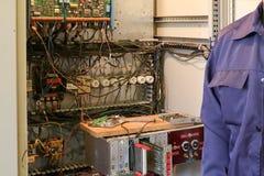 Um eletricista de trabalho masculino está na frente de um painel bonde com fios, transistor, fusíveis, eletrônica e interruptores foto de stock royalty free