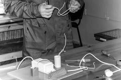 Um eletricista do homem que trabalha trabalhos, recolhe o circuito bonde de uma grande lâmpada de rua branca com fios, um relé em imagens de stock