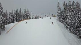 Um elevador de esqui em uma floresta em uma estância de esqui aumenta povos para a parte superior da montanha video estoque