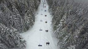 Um elevador de esqui em uma floresta em uma estância de esqui aumenta povos para a parte superior da montanha filme